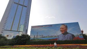 En kinesisk familj i staden Shenzhen går förbi en jättelik av affisch av Deng Xiaoping, som genomförde ekonomiska reformer i Kina i början av 1980-talet.