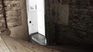 En trätrappa och tegelvägg som leder till en dörr till andra balkongen på Alexanderstatern.