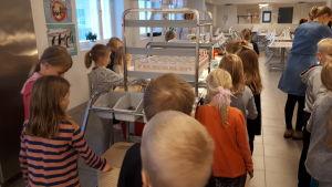 Elever i kö till skolmat i en matsal.