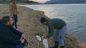 Tre personer fiskar i en by i Bosnien.