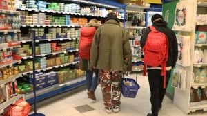 Tre personer inne i en matbutik. Bilden tagen bakifrån vid mjölkhyllan.