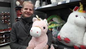 Anders Olin håller en rosa enhörning i famnen på ett varuhus.