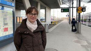 Maija Kaukonen står på perrongen på Helsingfors järnvägsstation. Hon ser in i kameran och ler litet. Bakom henne står tåg, och det är mulet. Hon har en brun jacka och en ljus halsduk.