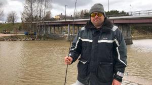En man med ett fiskespö vid Åstranden bredvid Mannerheimgatans bro.