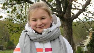 En 15-årig flicka med blont hår i hästsvans bak. Hon har en vit, vindtät jacka och grå halsduk på sig. Hon ser in i kameran och ler lite. Ett träd och ett hus i bakgrunden.