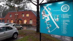 En turkos skylt med karta över Lauste familjerehabiliteringscenter, och huvudbyggnaden i rödtegel i bakgrunden.