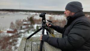 En man med vinterkläder står uppe i ett torn och fotograferar landskap