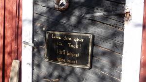 en svart skylt på en svartmålad trädörr. På skylten står det att man kan lämna sina gåvor där, på svenska och finska.