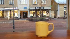 Kaffekopp i caféförnster mot gata