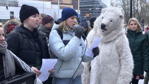 En demonstrant talar i mikrofon med en person i isbjörnsdräkt bredvid sig.