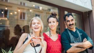Alina kahden ravintoloitsijan kanssa ravintolan edessä, näyttää sormillaan sydäntä.