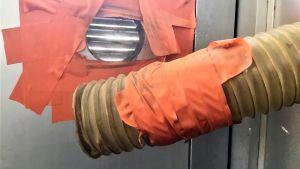 Ett ventilationsrör som har tejpats fast i en dörr med orangefärgad tejp. Men röret har lossnat.