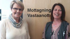 """Två leende kvinnor står mot en  stägd dörr där det står """"Mottagning Vastaanotto""""."""