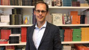 En man med glasögon står framför en bokhylla.