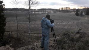 Jan Södersved kiikaroi muuttolintuja pellon laidalla.