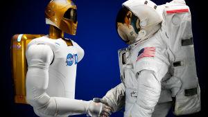 En astronaut och NASAS robot skakar hand