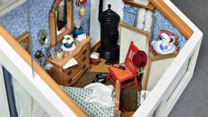 sovrummet består av säng, byrå, stol, speglar, klockor och smycken, en kamin, hattar och tavlor.