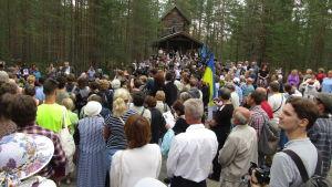 Hundratals människor står samlade i skogen framför ett stockhus på en kulle.