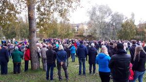 Många tiotals människor samlade till manifestation i höstlik miljö. De flesta har ryggen mot kameran.