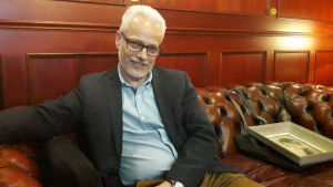 Specialisten Johan Wulff från Bukowskis sitter i ett bibliotek med mörkröda paneler på väggarna.