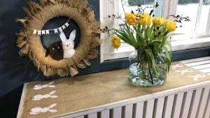 tulpaner i vas, duk med tryckt kaninmönster och en krans med kaniner på väggen bredvid ett fönster.