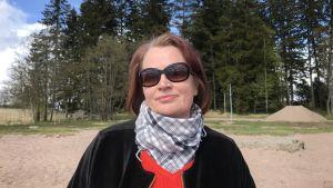 Kvinna iklädd solglasögon står och ler på en strand.