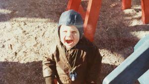 Stuba Nikula noin kaksivuotiaana leikkipuiston puuhevosen vierellä.