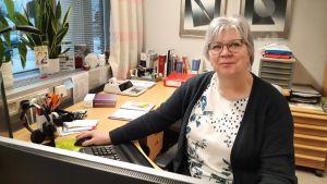 En kvinna med glasögon sitter vid ett skrivbord fullt med kanslimaterial.