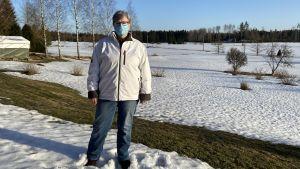 Siv står på sin gård i solen. I bakgrunden ser man en snöig åker.