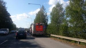 Brandbil och andra bilar på vägen. Björkar, vatten skymtar bakom träden, bro.
