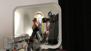 Anu Sinisalo står i en svart dress framför en spegel.
