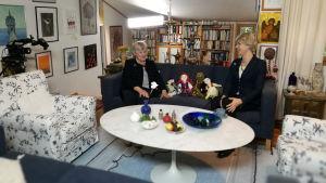 Elisabeth Rehn och Christoffer Strandberg sitter på en soffa. Christoffer är utklädd till Elisabeth i kavaj, peruk och pärlhalsband.