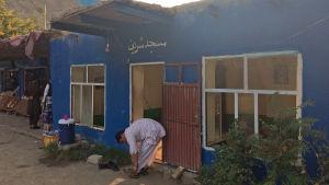 En muslimsk man knyter skorna framför ett blått hus i Afghanistan.