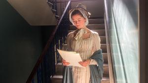 Nainen seisoo portaikon alapäässä ja lukee papereita.