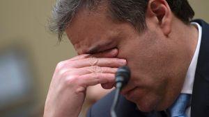 En trött och sorgsen Michael Cohen med ansiktet lutat i handen.