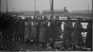 Människor bär en lång skena på ett koncentrationsläger.