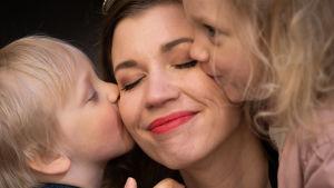 Lapset pussaavat äitiään poskelle.