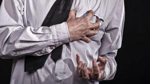 Man iklädd skjorta o slips tar sig för bröstet.