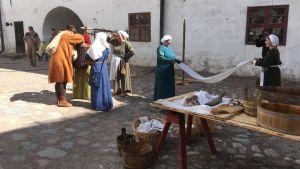 två kvinnor i medeltida dräkter tvättar byke på gården på Åbo slott under medeltidsevenemang.