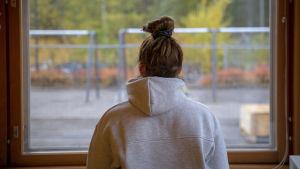 Tyttö katsoo koulun ikkunasta.