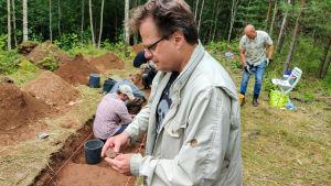 En man står vid en arkeologisk utgrävning och håller i två lerbitar.