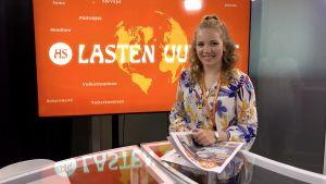 En ung leende kvinna framför en tv-skärm.