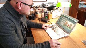 En man sitter vid en dator och behandlar bilder