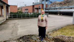 En kvinna står på en liten kulle framför en tegelbyggnad vid ett avloppsreningsverk.