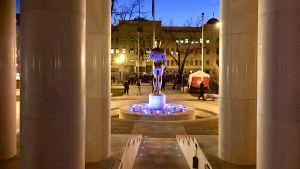 Ett ny staty i centrum av Skopje, Makedonien, fotad bakifrån och med en demonstration i bakgrunden.