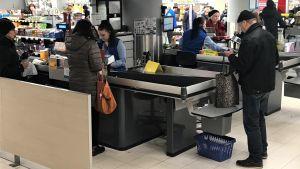 asiakkaat pakkaavat ostoksiaan S-marketissa