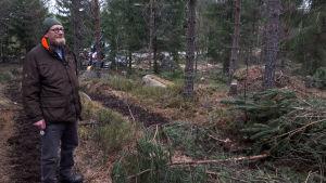 En man står på en skogsstig i en skog.
