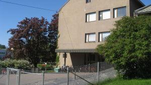 Beige betonghus i fyra våningar.