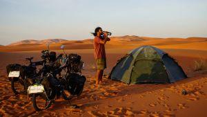 En man i öknen som står mellan ett tält och två cyklar