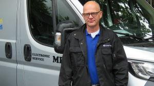 En man med glasögon,nästan utan hår står utanför en större paketbil.